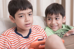 Little sibling boy playing game on mobile together at home Stock Photos
