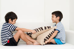 Little sibling boy playing pillow fighting on sofa Royalty Free Stock Photos