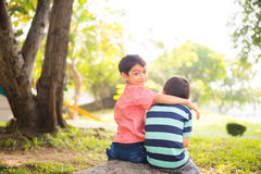 Little sibling boy sitting together in the park outdoor. Little sibling boy sitting together in the park Royalty Free Stock Photo