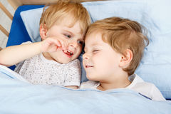 Little sibling boys having fun in bed at home Stock Photography