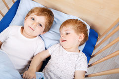 Little sibling boys having fun in bed at home Royalty Free Stock Images