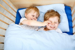 Little sibling boys having fun in bed at home Royalty Free Stock Photography