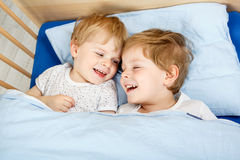 Little sibling boys having fun in bed at home Stock Photo