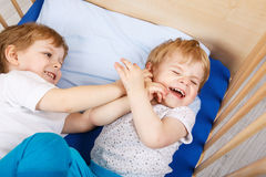 Little sibling boys having fun in bed at home Royalty Free Stock Photos