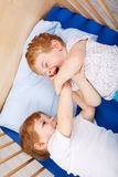 Little sibling boys having fun in bed at home Stock Image