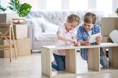 Little Siblings Assembling Wardrobe stock photography