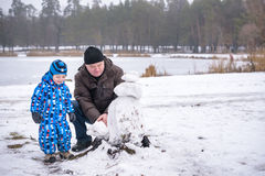 Little siblings boy making a snowman with grandfather, playing and having fun snow, outdoors on cold day. Active leisure children Stock Photo
