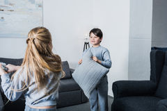 Little siblings in pajamas fighting with pillows at home. Cute little siblings in pajamas fighting with pillows at home Stock Photo