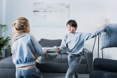 Little siblings in pajamas fighting with pillows at home. Cute little siblings in pajamas fighting with pillows at home Stock Photos