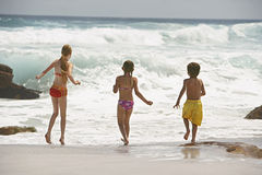 Little Siblings Running In Water Royalty Free Stock Photography