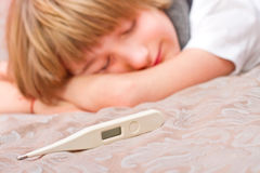 Little sick boy lying on bed with digital thermometer Royalty Free Stock Images