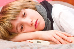 Little sick boy lying on bed with digital thermometer Stock Photos