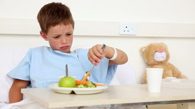 Little sick boy sitting in bed having lunch Stock Photo