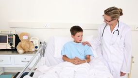 Little sick boy sitting in bed talking with doctor