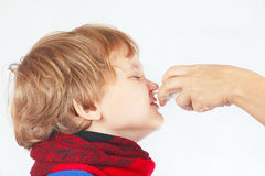 Little sick boy used medical nasal spray in the nose. On a white background Stock Photography