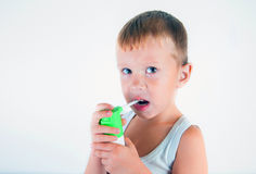 Little sick boy used medical spray for breath. little boy using his asthma pump. Use a spray for allergies. Cute baby enjoys the s Royalty Free Stock Photo