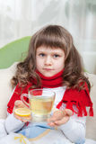 Little sick girl in bed is taking medicine. Close-up sympathetic little sick girl wrapped in red scarf under blanket in bed is drinking antiviral with lemon Stock Photography