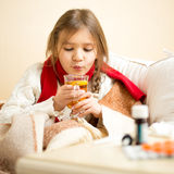 Little sick girl lying in bed and blowing on hot tea Stock Images