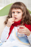 Little sick girl with scarf in bed Stock Images