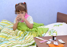The little sick girl sits in a bed and drinks water from a glass Stock Photo