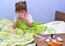 The little sick girl sits in a bed and drinks water from a glass Royalty Free Stock Image
