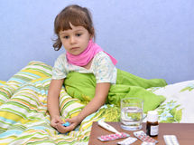 The little sick girl sits in a bed Royalty Free Stock Photos