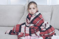 Little sick girl sits on a white couch wrapped in a red scarf. She is cold and she wrapped herself in a red blanket Royalty Free Stock Images