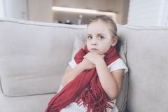 Little sick girl sits on a white couch wrapped in a red scarf. She has a very sore throat and she holds on to him Stock Image