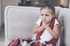 Little sick girl sits on a white couch wrapped in a red scarf. She has a very sore throat and she holds on to him Royalty Free Stock Photo