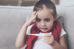 Little sick girl sits on a white couch wrapped in a red scarf. He looks at the thermometer, it has a high temperature Royalty Free Stock Photography