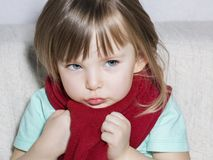 Little sick girl sits on a white couch wrapped in a red scarf. stock photo