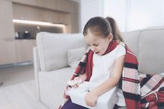 Little sick girl sits on a white couch wrapped in a red scarf. She sneezes, taking out a napkin. Little sick girl sits on a white couch wrapped in a red scarf Stock Photo