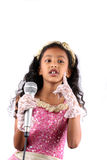 Little Singing Sensation. A portrait of a cute Indian girl in a singing performance, on white background Royalty Free Stock Image