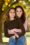 Little-Sister With Big-Sister Outdoors In Early Fall. 16 year old big sister hugging 12 year old little sister outdoors under trees in early fall Stock Photo