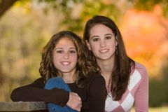 Little-Sister With Big-Sister Outdoors In Early Fall. 16 year old big sister beside 12 year old little sister outdoors under trees in early fall Royalty Free Stock Photos