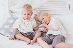 Little sister and brother sit on the bed stock photos