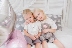Little sister and brother sit on the bed stock photography