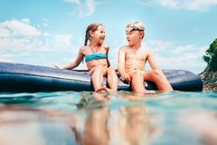 Little sister and brother sit on inflatable mattress in the sea stock images