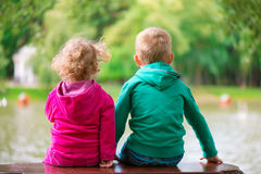 Little sister and brother sitting on bench at pond Royalty Free Stock Photos