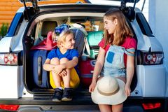 Family vacation suitcases Labrador dog girl boy kid baggage blue pink orange house sun summer luggage car ready holidays green tra. Little sister and brother are Stock Photos