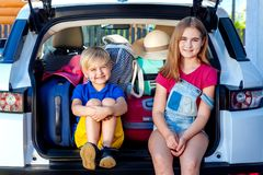 Family vacation suitcases Labrador dog girl boy kid baggage blue pink orange house sun summer luggage car ready holidays green tra. Little sister and brother are Royalty Free Stock Photography