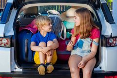 Family vacation suitcases Labrador dog girl boy kid baggage blue pink orange house sun summer luggage car ready holidays green tra. Little sister and brother are Stock Image