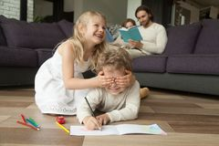 Sister closing brothers eyes with hands, family activities at ho Royalty Free Stock Image