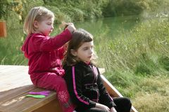 Little sister girls hairdresser on the river Royalty Free Stock Images
