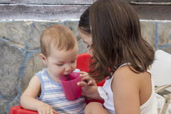 Little sister helping to her baby brother to drink Stock Photo