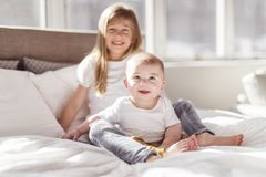 Little sister with her baby brother. Toddler kid Family with children at home. stock photos