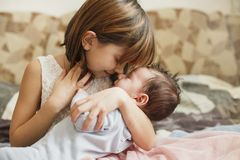 Little sister hugging her newborn brother. Toddler kid meeting new sibling. Cute girl and new born baby boy relax in a. Home bedroom. Family with children at stock photos