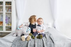 The little sister kisses the brother, staying at home on a bed in the light bedroom stock photography