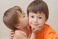 Little sister kissing older brother Royalty Free Stock Photo