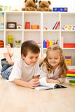 Little sister let me show you how to read. Kids with books laying on the floor Royalty Free Stock Image